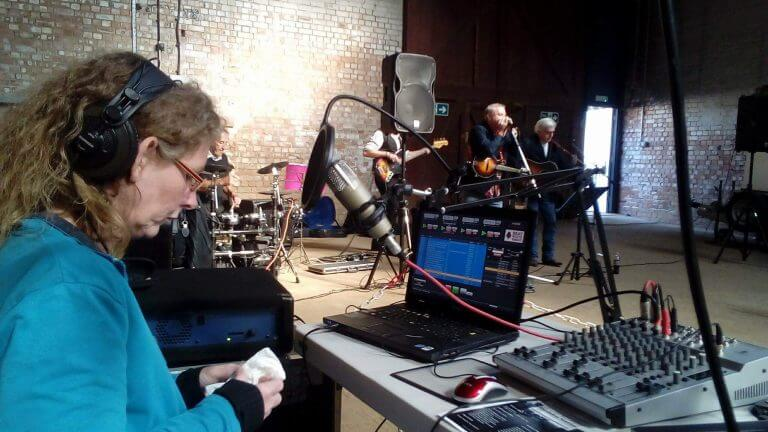 A radio microphone, with a mixing desk and a laptop on a table, with a presenter sitting at on a chair. Whilst a band plays music in a hall