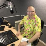 Paul - Presenter, behind the studio desk. In front of a microphone, on a chair smiling at the camera.
